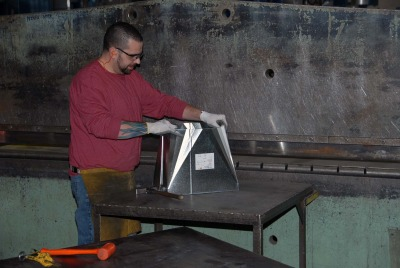 This is a photo of an employee manipulating sheet metal
